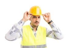 Konstruktör eller byggmästare som fixar hans hårda hatt för skyddsguling royaltyfri bild