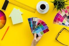 Konstruktörarbetsutrymme med paletten i hand-, linjal- och husdiagram på bästa sikt för gul bakgrund arkivfoto