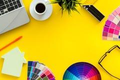 Konstruktörkontorsskrivbord med det hjälpmedel-, palett-, linjal-, bärbar dator- och husdiagramet på gul åtlöje för bästa sikt fö arkivfoto