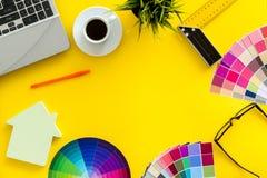Konstruktörkontorsskrivbord med det hjälpmedel-, palett-, linjal-, bärbar dator- och husdiagramet på gul åtlöje för bästa sikt fö royaltyfri bild