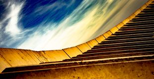 Konstruktion, abstrakt gul trappa och härlig himmel med vita moln arkivfoton