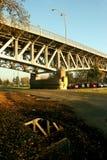 Konstruktion av bron reflekterade i en pöl Arkivfoton
