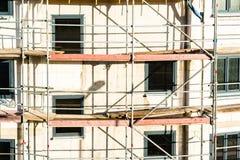 Konstruktion av det nya huset med materialet till byggnadsställning Arkivbilder