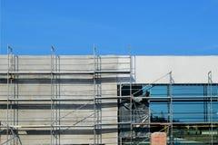 Konstruktion av en modern köpcentrum med en fasad av exponeringsglas och betong och en underjordisk parkering, i en solig dag med arkivbild
