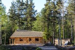 Konstruktion av ett härligt hus som göras av timmer och harmoniously att passa in i naturen arkivbilder