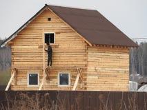Konstruktion av ett hus som g?ras av pl?terat fan?rbr?te ramen av huset Stuga som g?ras av pl?terat tr? Uppf?rande av royaltyfri bild