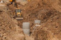 Konstruktion av ett nytt avloppsnätsystem Bulldozern gräver ett dike för avklopprör Byggnationer Arkivbild