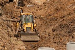 Konstruktion av ett nytt avloppsnätsystem Bulldozern gräver ett dike för avklopprör Byggnationer Arkivfoto