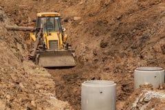 Konstruktion av ett nytt avloppsnätsystem Bulldozern gräver ett dike för avklopprör Byggnationer Fotografering för Bildbyråer