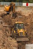 Konstruktion av ett nytt avloppsnätsystem Bulldozern gräver ett dike för avklopprör Byggnationer Royaltyfri Fotografi