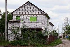 Konstruktion av ett vitt tegelstenhus utanför ett staket i en trädgård nära vägen Royaltyfria Foton