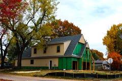 Konstruktion av huset för två berättelse i lövrik grannskap i höst arkivfoton