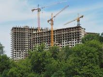 Konstruktion av mång--våning byggnader Hus och konstruktionskranar på himmelbakgrund De gröna träden som är främsta av arkivfoton