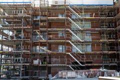 Konstruktion av nya lägenheter med materialet till byggnadsställning Royaltyfri Bild