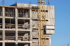 Konstruktion av ram-betong hyreshus med en höghuskran Lyft skjulet upp på bakgrunden av det oavslutat royaltyfri fotografi