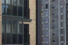 Konstruktion av ram-betong hyreshus med en höghuskran Lyft skjulet upp på bakgrunden av det oavslutat arkivfoto
