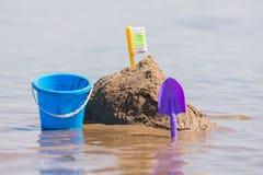 Konstruktion av sandslotten, som står bredvid en skyffel och en hink på, blir grund av floden Arkivfoto