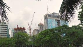 Konstruktion av skyskrapor i ett upptaget affärsområde Konstruktionskranar fungerar på byggandeplatsen arkivfilmer