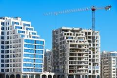 Konstruktion av två identiska högväxta byggnader av vita kvarter mot en klar blå himmel, kran, jämförelse Royaltyfri Foto
