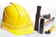 Konstruktion bearbetar, hardhaten och ritningen Fotografering för Bildbyråer