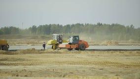 Konstruktion hårdna av flygplatslandningsbanavägar, huvudväg Män arbetare som arbetar med asfaltpaveren Roadroller stock video