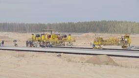 Konstruktion hårdna av flygplatslandningsbanavägar Män arbetare som arbetar med asfaltpaveren som vilar Roadroller arkivfilmer