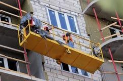 Konstruktion inställde vaggan med arbetare på ett nybyggt höghus royaltyfri fotografi