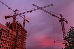Konstruktion lyftande kran på skymning på solnedgången Fotografering för Bildbyråer