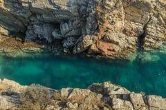 Konstruktion med den ärke- steniga kusten & det genomskinliga havet royaltyfri fotografi