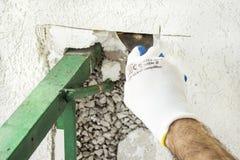 konstruktion skriver in inte arbetszon Polystyrenisolering av byggnaden Arbetaren tar bort styckena av polystyrenen Royaltyfri Foto