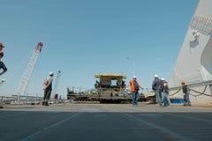 Konstruktionen av den Crimean bron Asfaltstenläggning Vägarbeten på bron arkivfoton