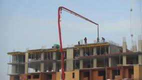 Konstruktionen av en flervånings- hyreshus 4K Byggnadsarbetare häller konkreta golv, konstruktion arkivfilmer