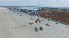 Konstruktionen av flygplatsen med landningsbanan Den flyg- sikten av flygplatslandningsbanan blir en konstruktionsplats arbetare  Arkivfoto