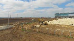 Konstruktionen av flygplatsen med landningsbanan Den flyg- sikten av flygplatslandningsbanan blir en konstruktionsplats arbetare  Arkivfoton