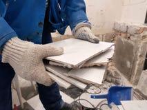 Konstruktionsavfalls och gammal tegelplatta i hand fotografering för bildbyråer
