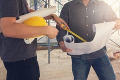 Konstruktionsbegrepp, tekniker och arkitekt som arbetar på konstruktionsplatsen med ritningen Arkivfoton