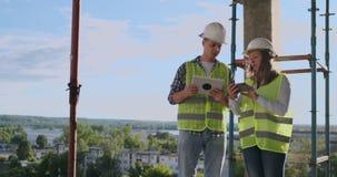 Konstruktionschef och tekniker som arbetar p? byggnadsplats lager videofilmer
