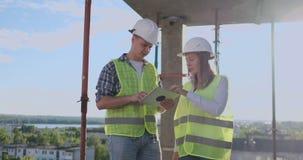 Konstruktionschef och tekniker som arbetar p? byggnadsplats stock video