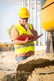 Konstruktionschef som kontrollerar byggnadsplatsen med plan Royaltyfria Bilder