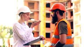 Konstruktionschefen kontrollerar arbetsprocessen i konstruktionsbranschen En kvinnlig tekniker meddelar med a arkivfilmer