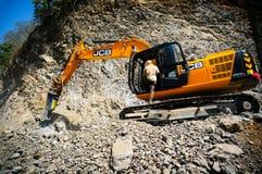 Konstruktionsgrävskopan som gör klar upp, vaggar från en jordskred Royaltyfri Fotografi