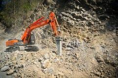 Konstruktionsgrävskopan som gör klar upp, vaggar från en jordskred Royaltyfria Bilder