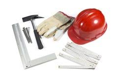 Konstruktionshjälpmedel - den skyddande hardhaten, handskar, hammare, spikar och riktlinjalen som isoleras på vit Royaltyfri Bild