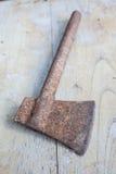 Konstruktionshjälpmedel, gammal rostig yxa på den wood tabellen Royaltyfri Fotografi