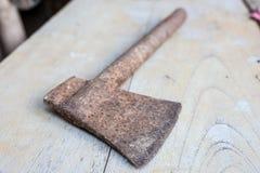 Konstruktionshjälpmedel, gammal rostig yxa på den wood tabellen Fotografering för Bildbyråer