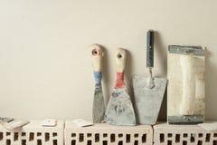 Konstruktionshjälpmedel i rad och tegelstenar Byggnad och renoveringbegrepp Arkivfoton