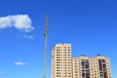 Konstruktionskran nära det nybyggda flerbostadshuset Arkivfoto