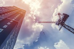 Konstruktionskran och höjdbyggnadsandelslägenhet arkivfoto