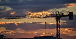 Konstruktionskran på solnedgången Arkivfoton