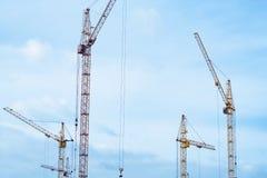 Konstruktionskranar bygger hus royaltyfria bilder